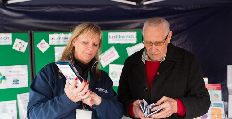 Man and woman looking at Healthwatch leaflets