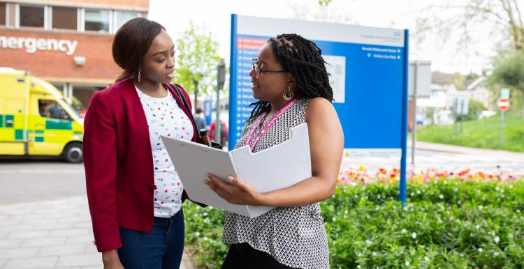 A Healthwatch volunteer with a clipboard speaking to a woman outside a hospital