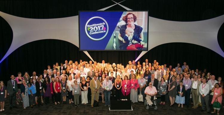 A large group of people standing underneath a banner for the Healthwatch 2017 conference