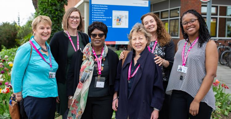 A group of women wearing Healthwatch badges standing outside a hospital