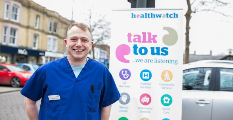 NHS worker standing infront of a Healthwatch 'talk to us' sign