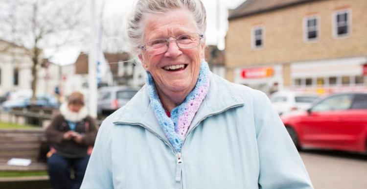 Elderly woman smiling at camera from community event