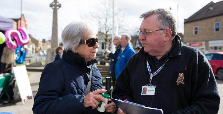 A woman speaking to a man with a clipboard