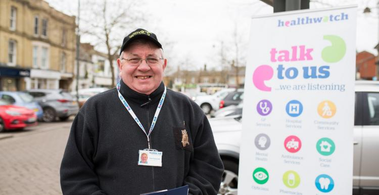 An older man wearing a hat standing infront of a poster promoting Healthwatch