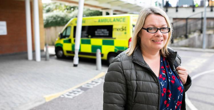 A blonde woman in a coat, standing in front of an ambulance