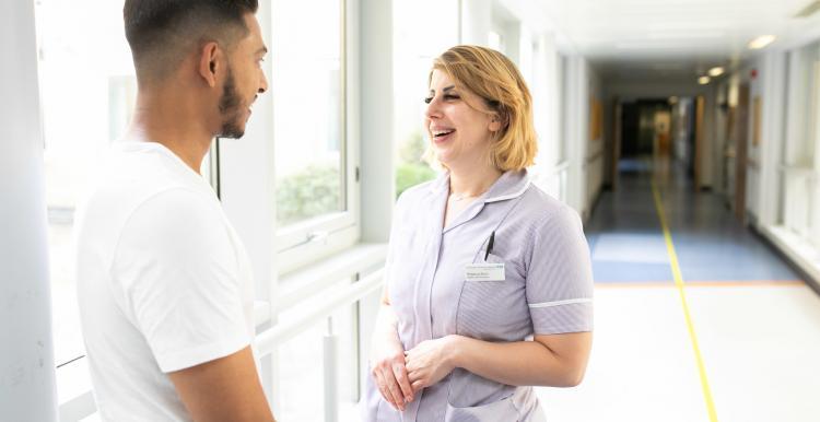 A young man talking to a nurse in a corridor