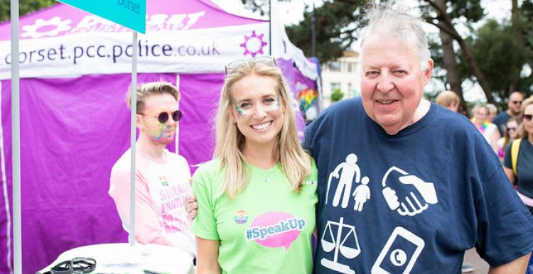 Older man with his arm round a younger woman at Bournemouth Pride. They are both smiling.