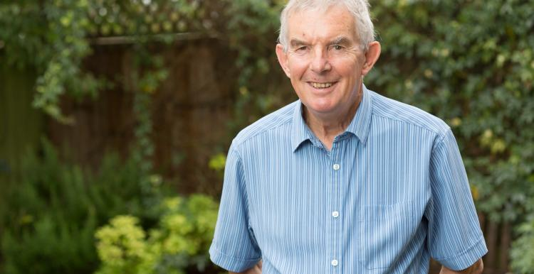 An older man in a blue shirt standing in a garden