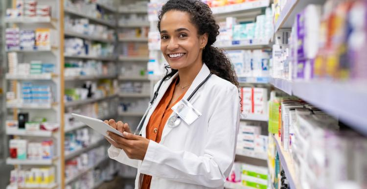 Young female pharmacist. She is wearing a white lab coat and orange shirt. Her hair is tied back. She is holding a tablet.