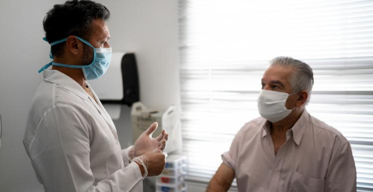 Male patient sitting on a hospital bed and talking to a male doctor. Both are wearing face masks.