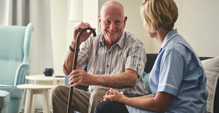 Man with a walking stick talking to a home care worker