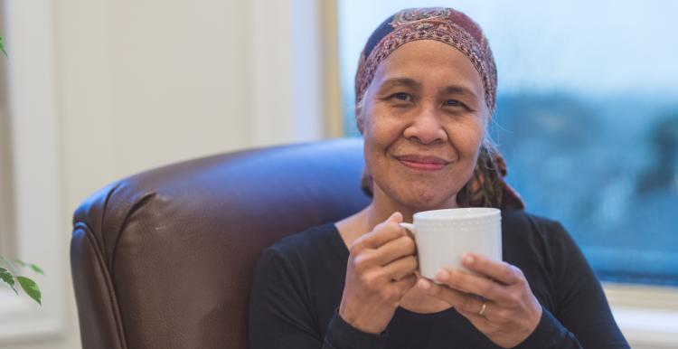 Elderly woman weaing a headscarf after chemotherapy drinking a cup of tea