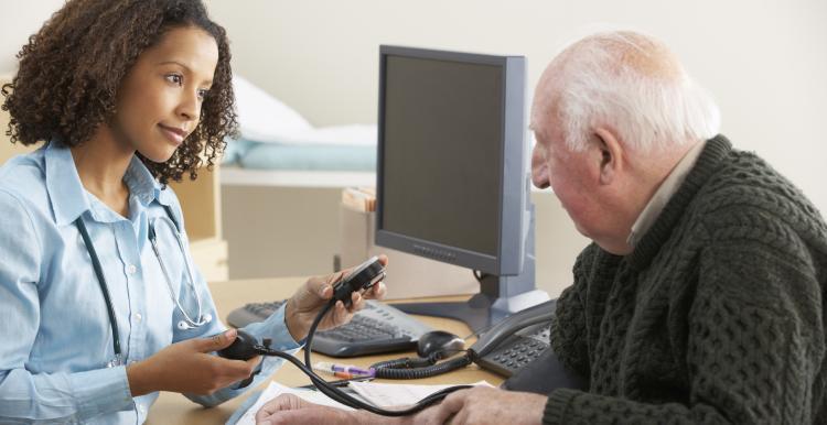 Female GP takes blood pressure of older man