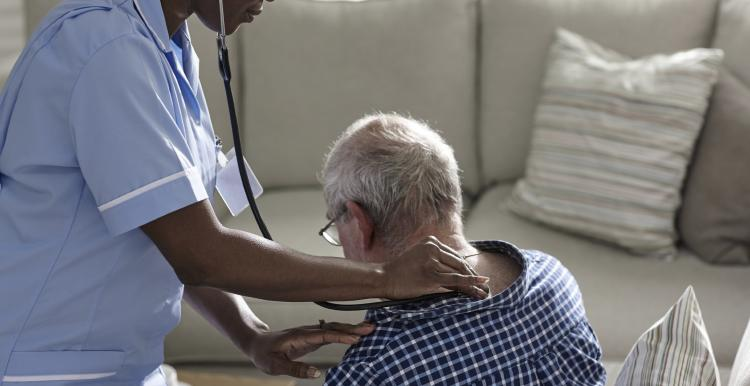 Nurse holding a stethoscope on a man's back in his home