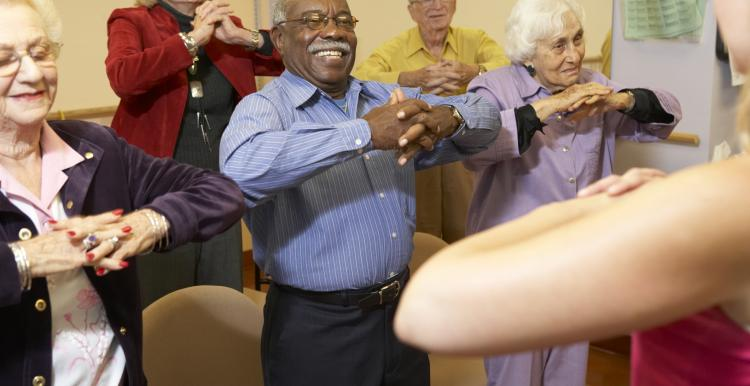 Elderly people in a care home doing group exercise