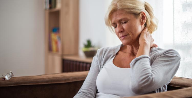 A woman rubbing the back of her neck