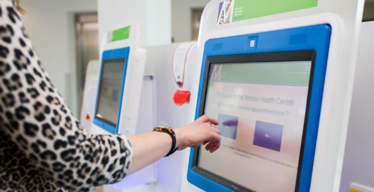 A women using a registration machine in a hospital