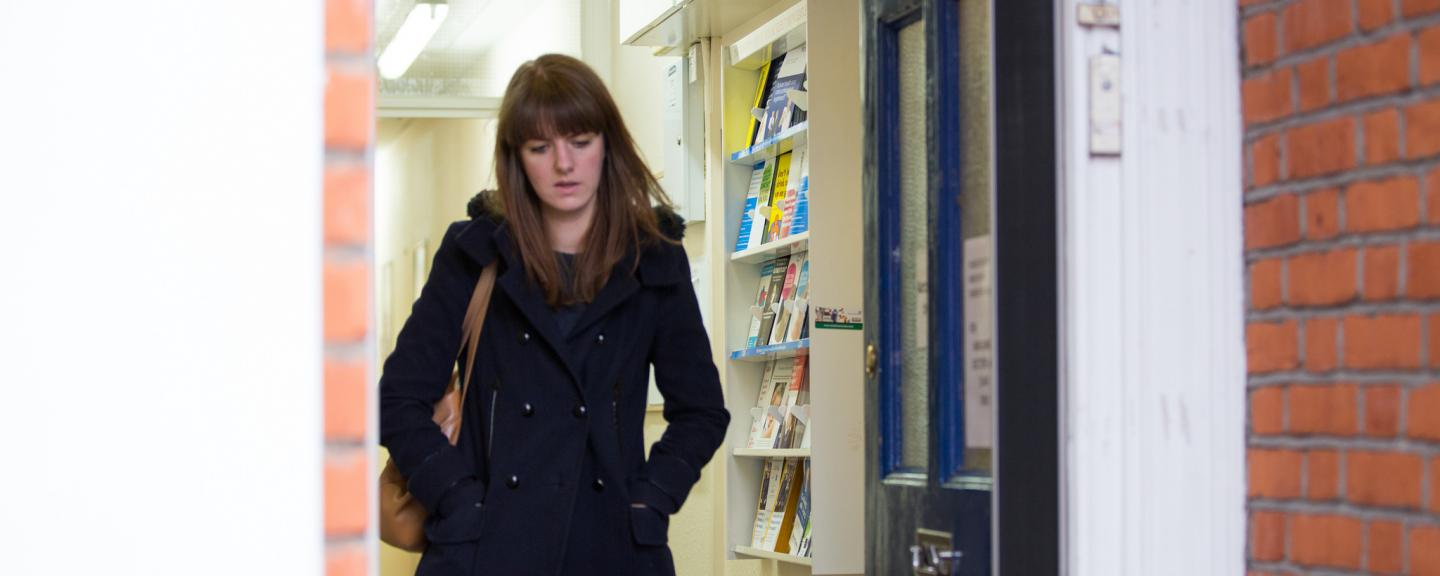 Woman walking out of a GP surgery with a neutral expression