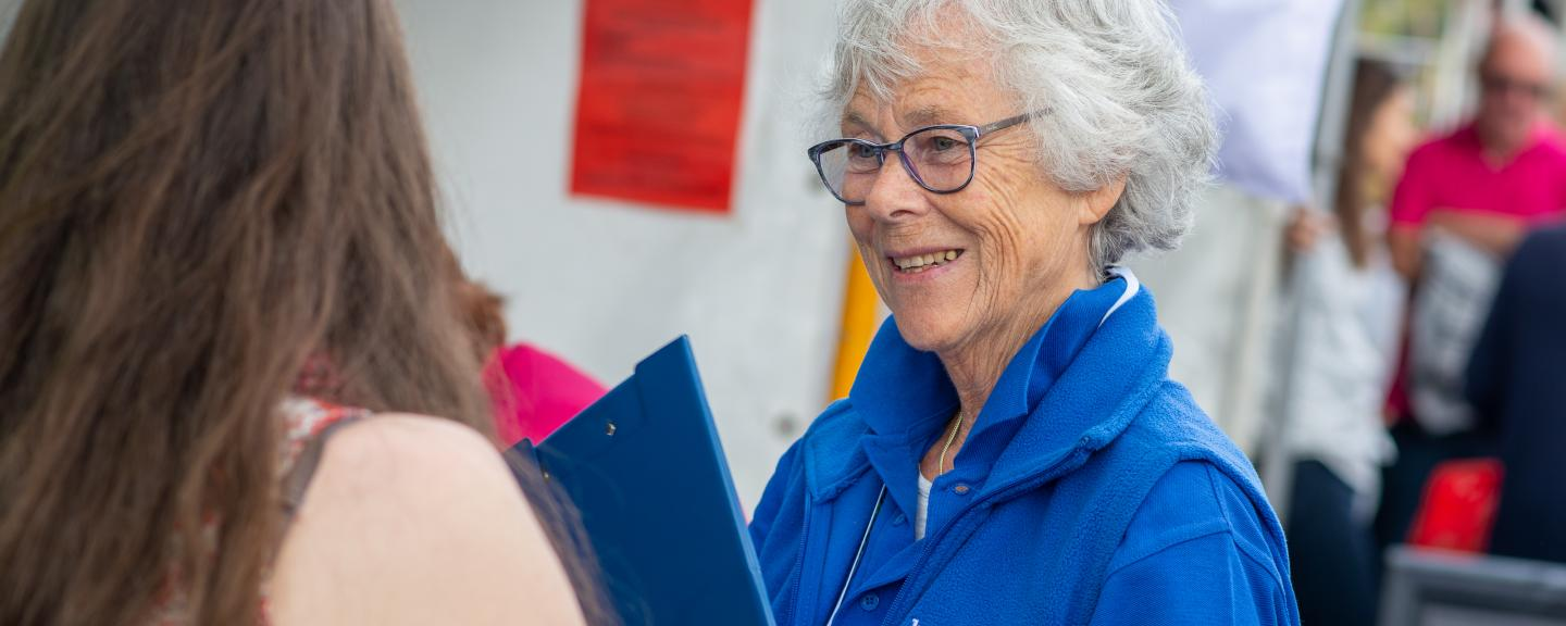 Healthwatch volunteer with a clipboard talking