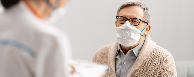 Doctor and senior man wearing facemasks during coronavirus outbreak.