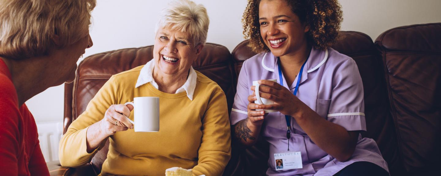 Two older ladies laughing with their nurse in a care home