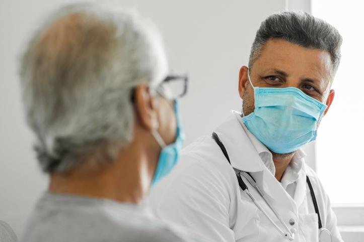 Male doctor talking to a senior patient at home