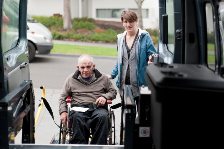 Man in wheelchair being helped into a minibus