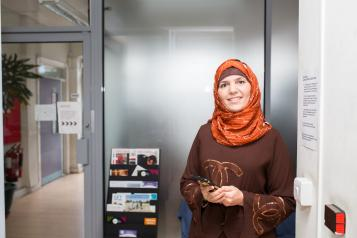 Woman wearing a headscarf and holding a smart phone