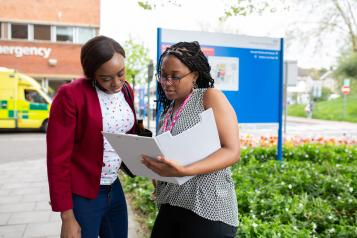 Two women look at a file whilst standing outside a hospital