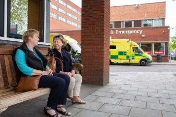 Two older women sitting on a bench outside hospital