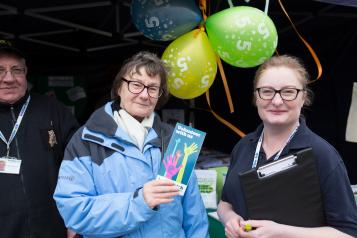Two Healthwatch volunteers at a stall with Healthwatch balloons