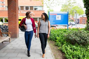 Two young women walking and talking outside a hospital