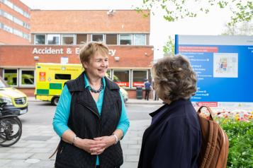 Two women talking outside a hospital
