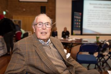 An older man in a brown check blazer and glasses, sitting down in a community hall.