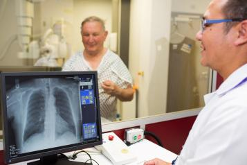 Radiographer helping a male patient