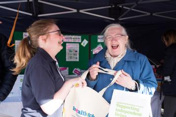 A Healthwatch volunteer laughing with an older lady at an event