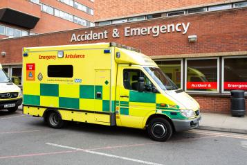 An ambulance parked outside the front of an A&E department in a hospital