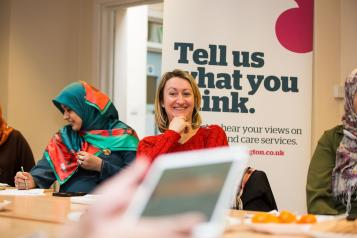 Group of healthwatch staff laughing while using laptops