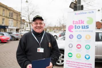 A man with a clipboard standing in front of a Healthwatch sign