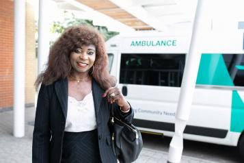 A woman with a handbag on her shoulder, standing in front of an ambulance