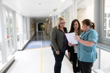 Three people in a hospital corridor. Two people speaking to a nurse