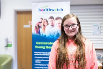 Young girl in front of Healthwatch sign