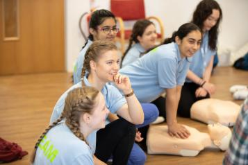 Teenage girls taking part in first aid session.