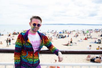 Man wearing multicoloured face paint stood in front of a beach