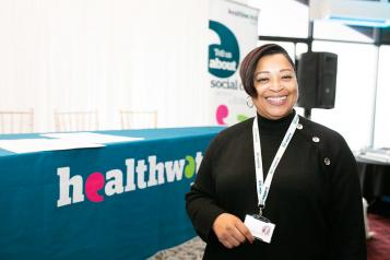 A women in front of a Healthwatch stand