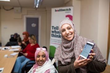 A women smiling and holding up her phone.
