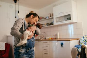 Woman holding baby in her kitchen