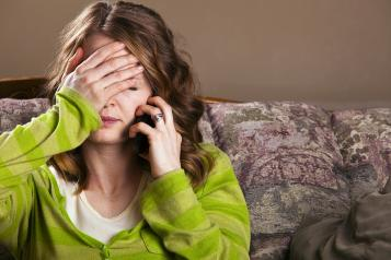 woman sitting on a sofa and with her right hand on her face and her left hand holding the phone near her left earbust picture of woman sitting on a sofa and with her right hand on her face and holding the phone near her left ear