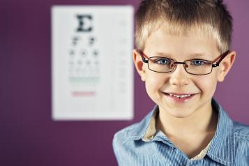 front picture of child with glassed and the eye test board on the background