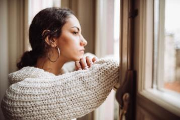Women looking at out of window, looking pensive